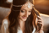 Portrait of beautiful and fashionable brunette model girl with charming smile, with trendy jewelry on her head and with professional bright makeup