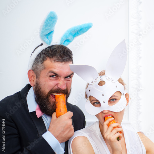 Leinwanddruck Bild Surprised bunny couple wearing bunny ears and eat carrot. Sexy easter.