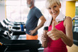 Happy senior people running together on treadmills in gym. - 247746767