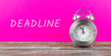 alarm clock with pink background with text deadline