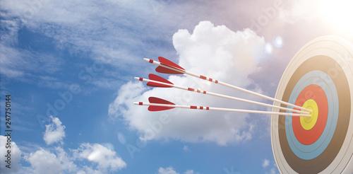 Leinwanddruck Bild Zielscheibe mit 3 Pfeilen vor einem blauen Himmel
