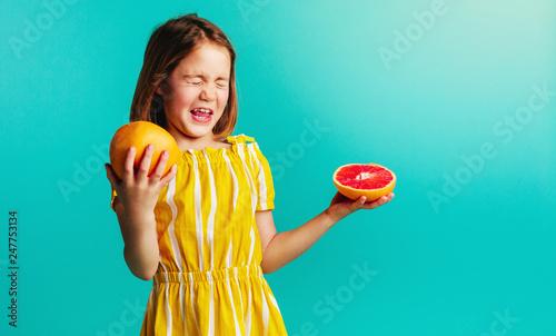 Leinwandbild Motiv Girl does not like the taste of grapefruit