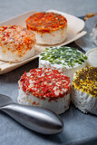 Assortment of French fresh white soft goat cheeses with different tastes topping made with herbs, paprika, indian curry, bruscetta, chives and dried tomatoes - 247759147