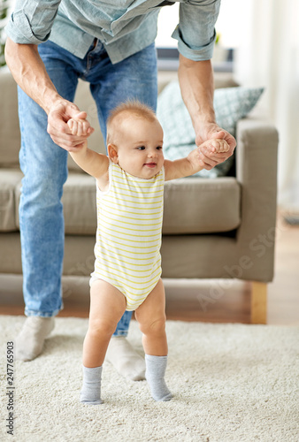 Leinwandbild Motiv family, toddling and babyhood concept - father helping little baby daughter with walking at home