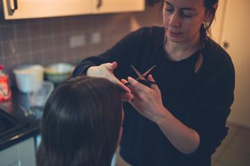 Woman cutting friend's hair in kitchen © LoloStock
