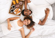 Leinwanddruck Bild - Happy black couple enjoying breakfast in bed