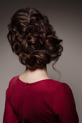 Back view of unrecognizable female turned back at camera. Woman in red dress after beauty salon with stylish haircut. Dark gray studio background.