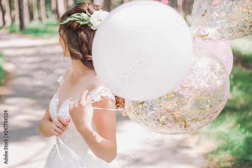 Leinwanddruck Bild Beautiful young bride holding several air balloons in hands while standing outside on sunny warm day. Horizontal color photography.