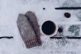 Cozy winter decoration with cup of black coffee and grey knitted mittens in snowy wooden background