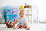 Cute little toddler child in sunny living room playing with  Easter chocolate bunny and colorful Easter eggs - 247788330