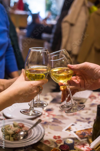 White wine in glasses on a table in a restaurant where a group of friends or family is having dinner - 247788965