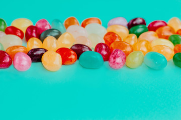 Colorful bean sweet candies on turquoise blue background. Easter concept. Close up. Copy space.