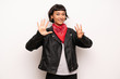 Leinwanddruck Bild - Woman with leather jacket and handkerchief counting eight with fingers