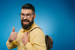 cheerful bearded man with backpack showing thumb up, isolated on blue