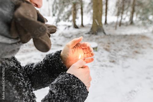 Leinwandbild Motiv Frau / Mädchen heizt Hände mit Feuerzeug in Kälte zum aufwärmen