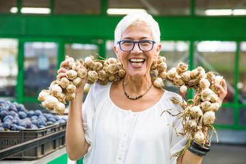 Senior woman buying lot of garlic on market