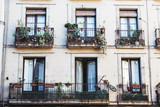 Façade d'un immeuble avec des balcons fleuris - 247819588