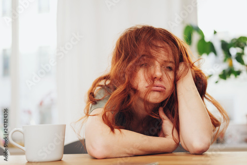 Red-haired girl sitting at table with boring face