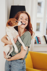 Laughing woman holding her pet dog