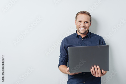 Foto Murales Attractive friendly man holding an open laptop