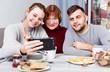 Leinwandbild Motiv Young couple making selfie with senior woman