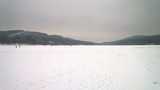 Photo of a large frozen lake covered in snow and surrounded by hills - 247831361