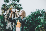 Young blond woman on vacation take picture with smartphone in the park. - 247831962