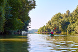 Woman in elegant straw hat canotier paddling green kayak at Danube river at summer. Concept of recreation and adventure