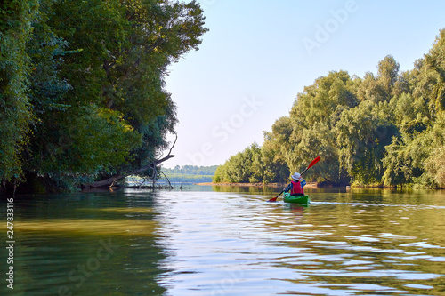 Leinwandbild Motiv Woman in elegant straw hat canotier paddling green kayak at Danube river at summer. Concept of recreation and adventure