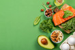 Keto diet concept - salmon, avocado, eggs, nuts and seeds, bright green background, top view