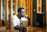 Handsome african man drinking a coffee in establishment.