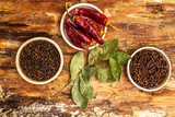 Set of spices - black pepper peas, clove, hot red pepper and bay leaf. On wooden bark, top view, close up.