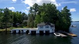 A white lakeside cottage with multiple boat garages. - 247879528