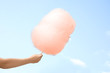 Leinwanddruck Bild - Woman holding orange cotton candy against blue sky
