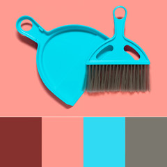 Color matching palette. A pale blue dustpan and brush lying on living coral background. In the style of pop art. Top view. Copy space.