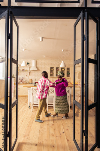 Happy delighted couple dancing in the kitchen - 247894984
