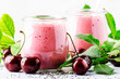 Leinwanddruck Bild - Pink cherry milkshake or smoothies with fresh berry and chia seeds, white stone kitchen background, place for text, top view