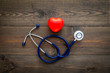 Heart health, health care concept. Stethoscope near rubber heart on dark wooden background top view copy space