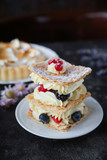 Tea and sweets on a dark background, Mille-feuille, Eclairs, Tart, Decorative with flowers, Selective focus, Closeup - 247912523