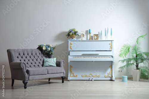 Interesting spring interior in a photo studio against a white wall of a blue piano with blue candles and a gray classic sofa © pridannikov
