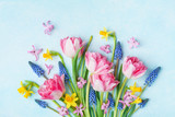 Bouquet of beautiful spring flowers on pastel blue table top view. Greeting card for International Women Day. Flat lay.