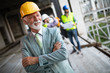 Confident construction engineer, architect, businessman in hardhat on building site - 247937737