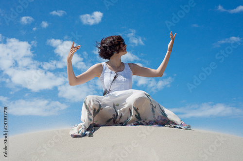 Foto Murales Woman sits on the sand and meditates