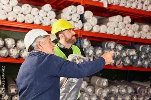 Leinwanddruck Bild Zwei Lagerarbeiter arbeiten im Teppichlager