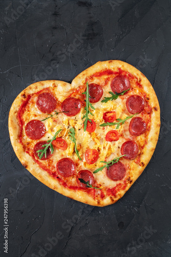Heart shaped pizza with meat and vegetables. Food concept of romantic love for Valentines Day. - 247956398