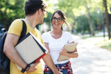 Young student couple going to college class.They walks trough university campus and laughing. - 247960300