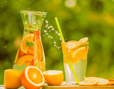A carafe and a glass with an illuminating summer drink  lemonade and various fruits against the backdrop of a green garden.