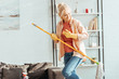 Funny senior woman playing mop guitar while cleaning house