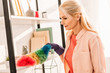 Senior woman in rubber glove cleaning shelves with bright duster