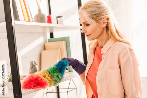 Leinwanddruck Bild Senior woman in rubber glove cleaning shelves with bright duster